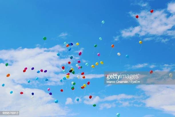 low angle view of helium balloons flying against blue sky - luftballons himmel stock-fotos und bilder