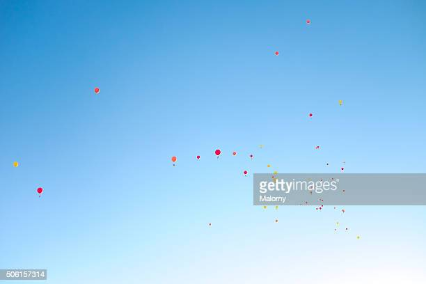 Low angle view of helium balloons with messages in mid-air against sky. Wedding.