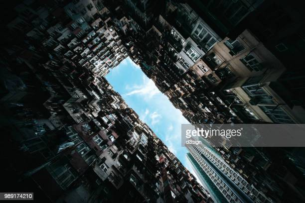 low angle view of high density old traditional residential blocks and highrise modern buildings against clear blue sky - skyscraper film stock pictures, royalty-free photos & images