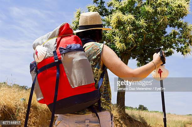 low angle view of hiker in hat with backpack walking against sky during sunny day - cammino di santiago di compostella foto e immagini stock