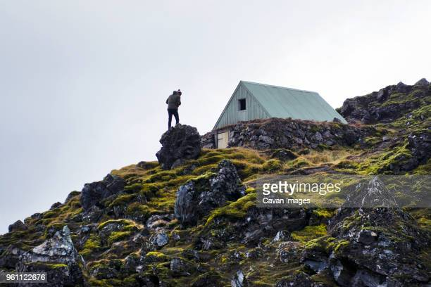 low angle view of hiker standing on rock against clear sky - hut stock pictures, royalty-free photos & images