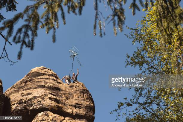 low angle view of hikers on cliff against clear blue sky - andrea rizzi stock pictures, royalty-free photos & images