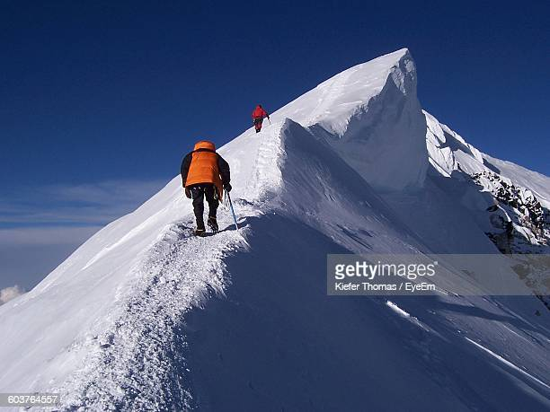 Low Angle View Of Hikers On Snow Covered Mountains