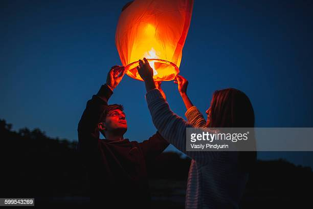 Low angle view of hikers releasing paper lanterns