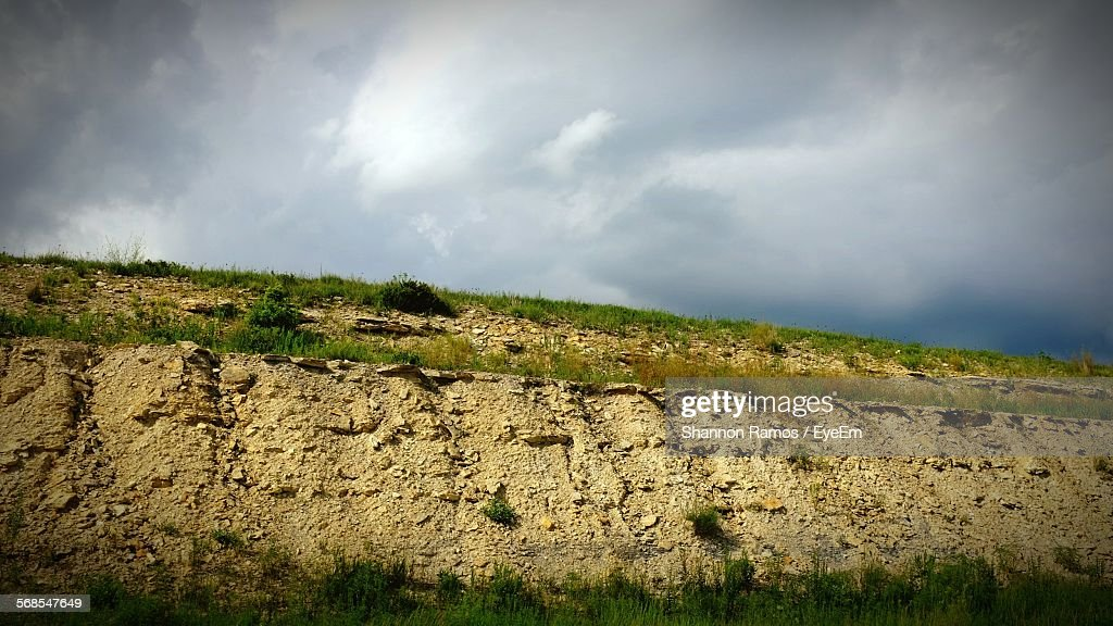 Low Angle View Of Hill Against Cloudy Sky : Stock Photo