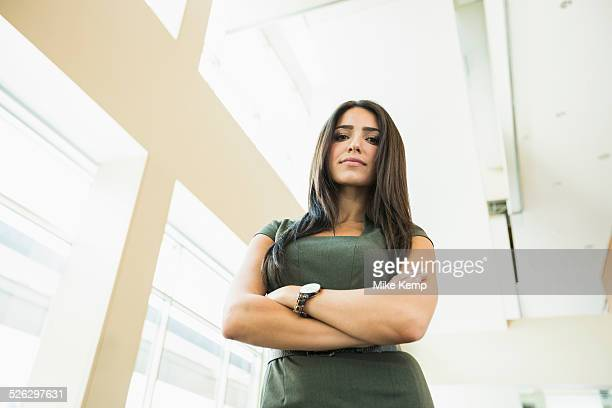low angle view of hispanic businesswoman standing in office - vista de ángulo bajo fotografías e imágenes de stock