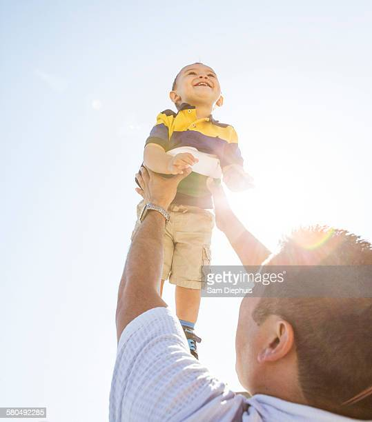 Low angle view of Hispanic father lifting son in air