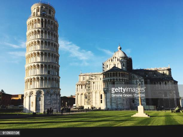 low angle view of historical building against blue sky - leaning tower of pisa stock photos and pictures