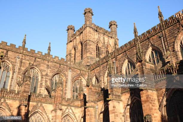low angle view of historical building against clear sky - chester cathedral stock pictures, royalty-free photos & images