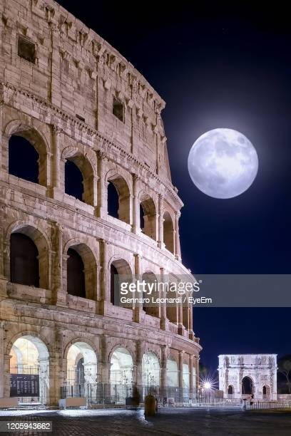 low angle view of historical building at night. coliseum and full moon - empire stock pictures, royalty-free photos & images