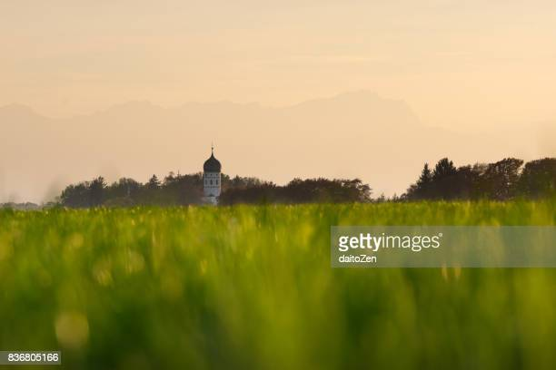 Low angle view of Holzhausen church bell tower, Wetterstein mountains with Zugspitze mountain in background, Holzhausen, Upper Bavaria, Germany