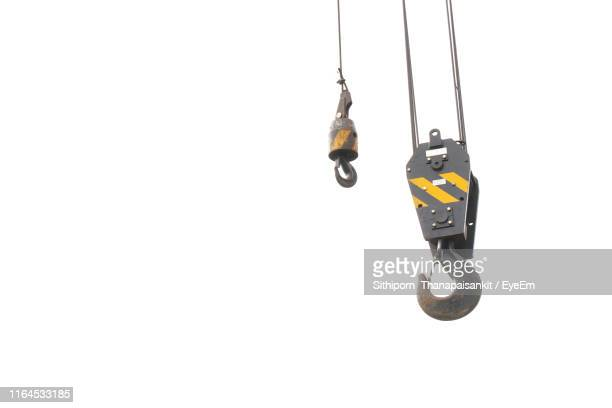 low angle view of hooks against white background - kran stock-fotos und bilder