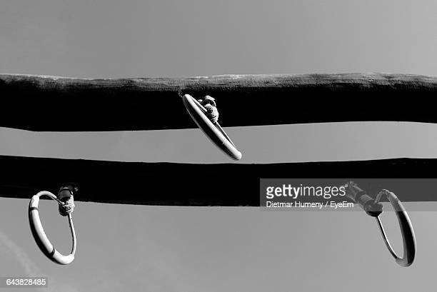 Low Angle View Of Hooks Attached On Wood Against Sky