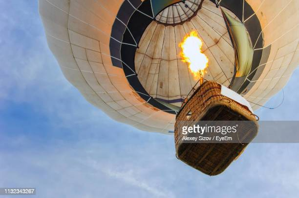 low angle view of hot air balloon against sky - balloon ride stock pictures, royalty-free photos & images