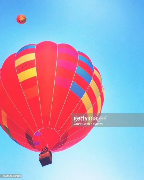 low angle view of hot air balloon flying against clear blue sky - australian capital territory stock pictures, royalty-free photos & images