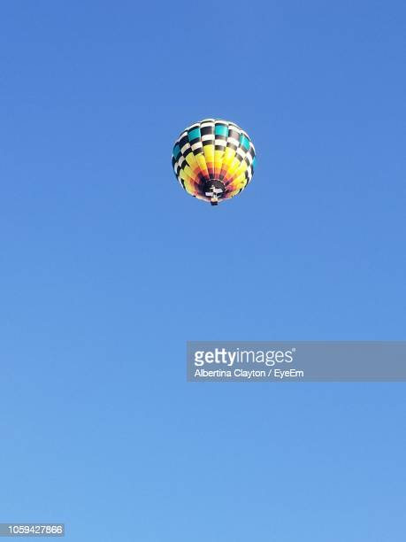 low angle view of hot air balloon flying against clear blue sky - albertina dias fotografías e imágenes de stock