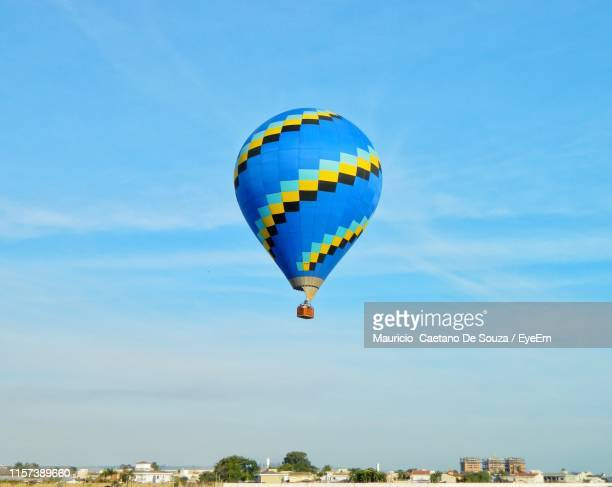 low angle view of hot air balloon flying against sky - mauricio caetano de souza stock photos and pictures