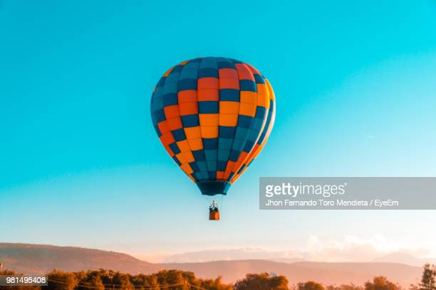 low angle view of hot air balloon flying in mid-air against clear blue sky - balloon ride stock pictures, royalty-free photos & images
