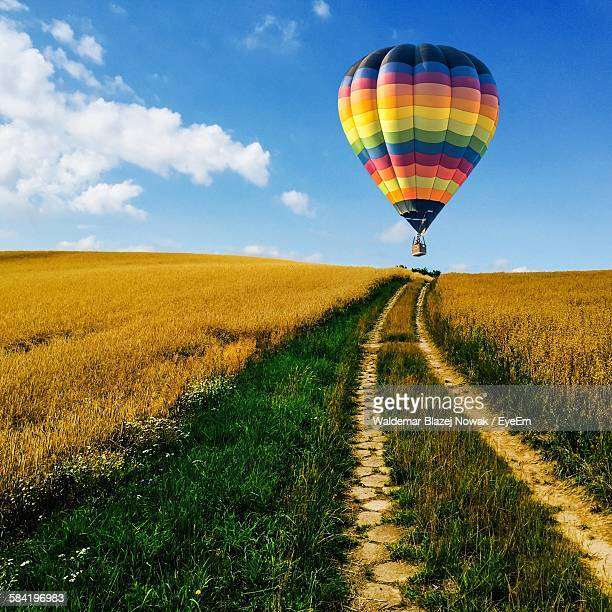 Low Angle View Of Hot Air Balloon Flying Over Agricultural Field Against Sky