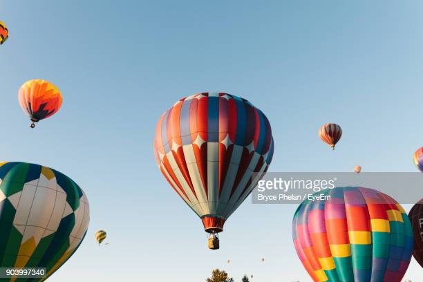 low angle view of hot air balloons against clear sky - balloon fiesta stock pictures, royalty-free photos & images