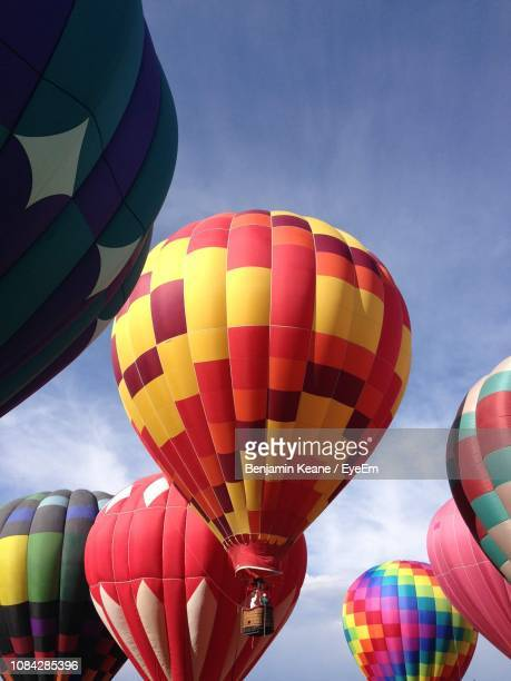 low angle view of hot air balloons against sky - balloon fiesta stock pictures, royalty-free photos & images