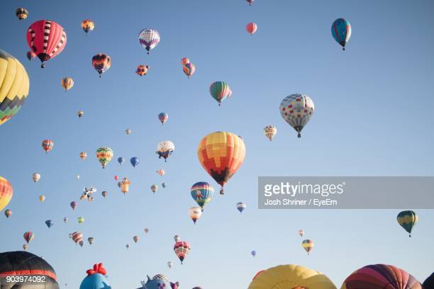 low angle view of hot air balloons in clear sky - balloon ride stock pictures, royalty-free photos & images