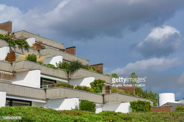 low angle view of house and building against sky - angela rohde stock-fotos und bilder
