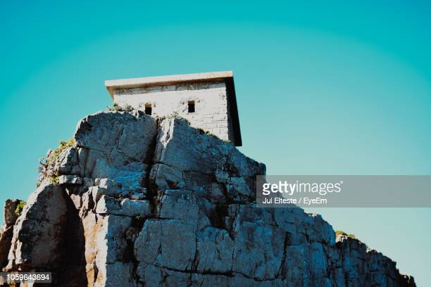 Low Angle View Of House On Cliff Against Clear Blue Sky