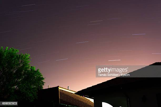 Low Angle View Of Houses Against Star Trails