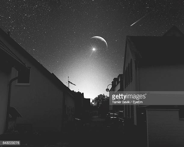 Low Angle View Of Houses Against Stars And Crescent Moon In Sky At Night