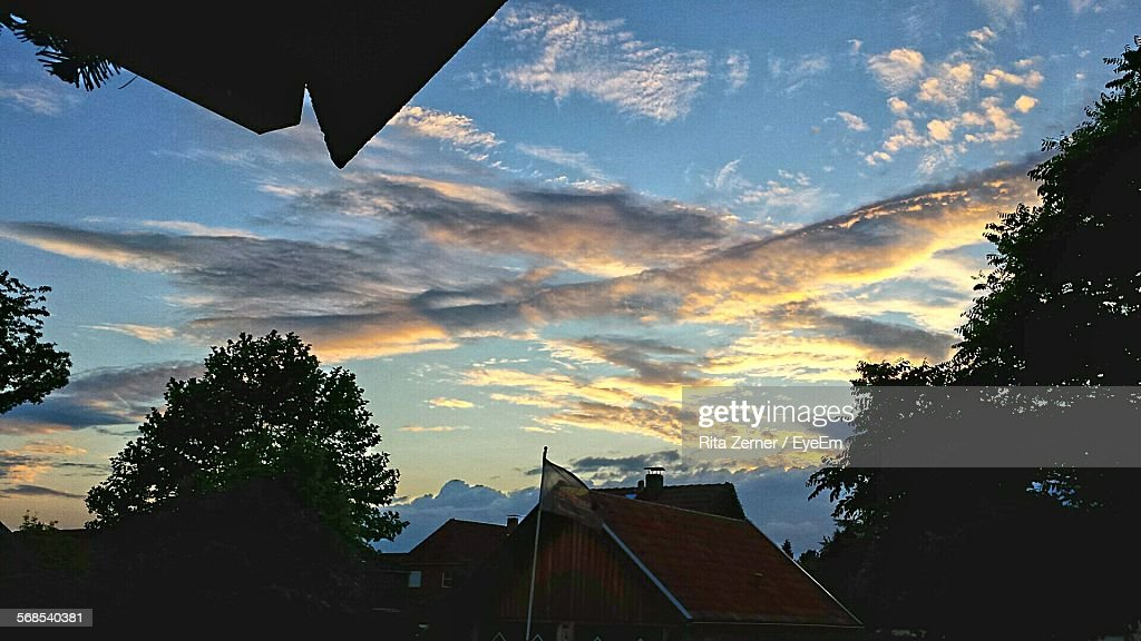Low Angle View Of Houses By Trees Against Cloudy Sky : Stock Photo