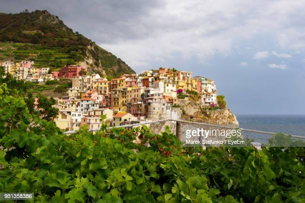 low angle view of houses on mountain by sea against cloudy sky - marek stefunko stockfoto's en -beelden