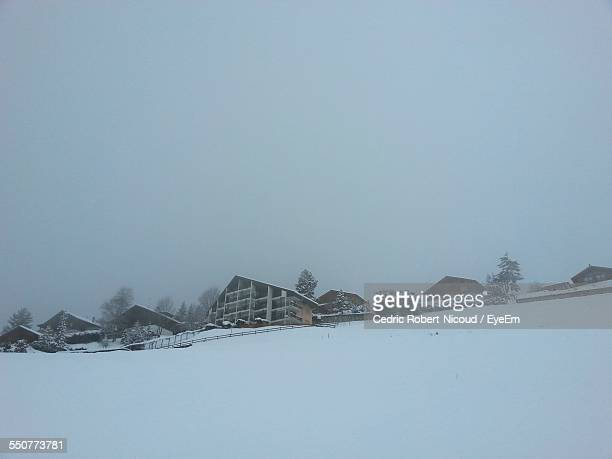 low angle view of houses on snow covered landscape against sky - leysin stock photos and pictures