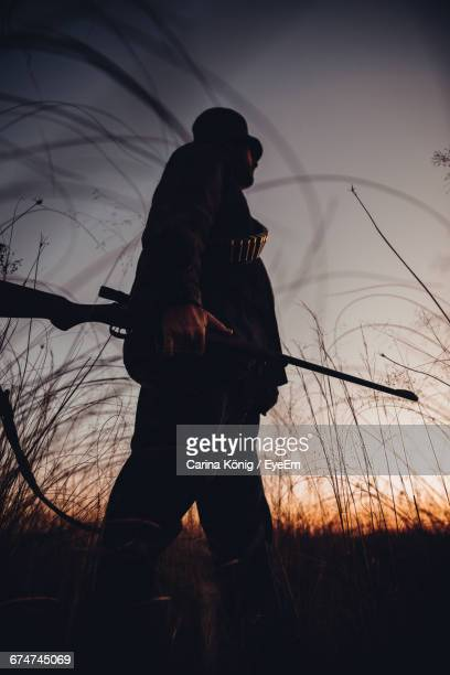 Low Angle View Of Hunter With Shotgun Walking In Field During Sunrise