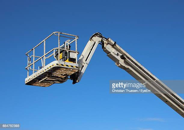 Low Angle View Of Hydraulic Platform Against Clear Blue Sky On Sunny Day