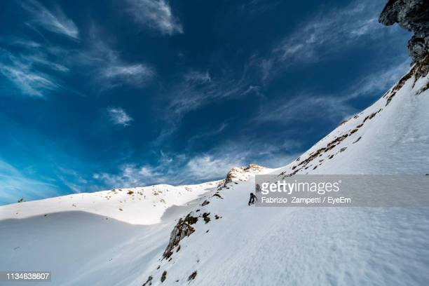 low angle view of ice climbers on snowcapped mountain - fabrizio zampetti foto e immagini stock