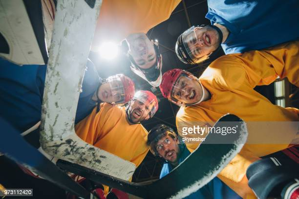 low angle view of ice hockey team making tough facial expressions. - ice hockey player stock pictures, royalty-free photos & images