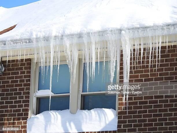 low angle view of icicles on house angle view of icicles on house - solomon turkel stock pictures, royalty-free photos & images