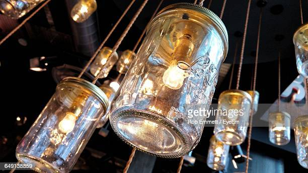 Low Angle View Of Illuminated Antique Jar Lights Hanging At Store