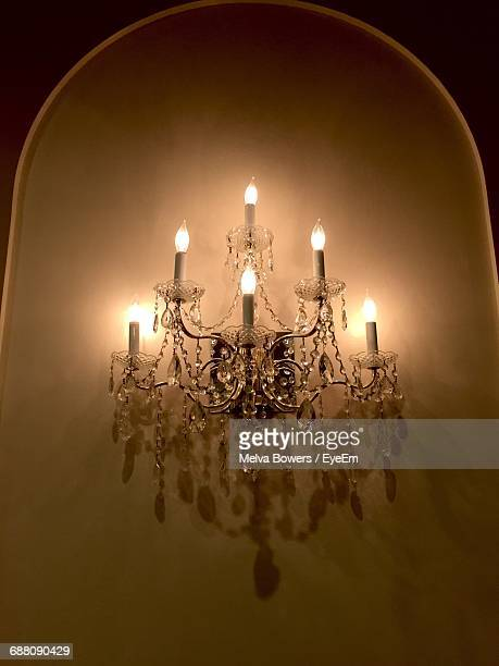 Low Angle View Of Illuminated Antique Sconce On Wall