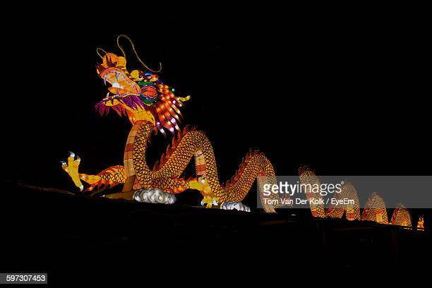 low angle view of illuminated artificial dragon against sky at night - chinese dragon stock pictures, royalty-free photos & images