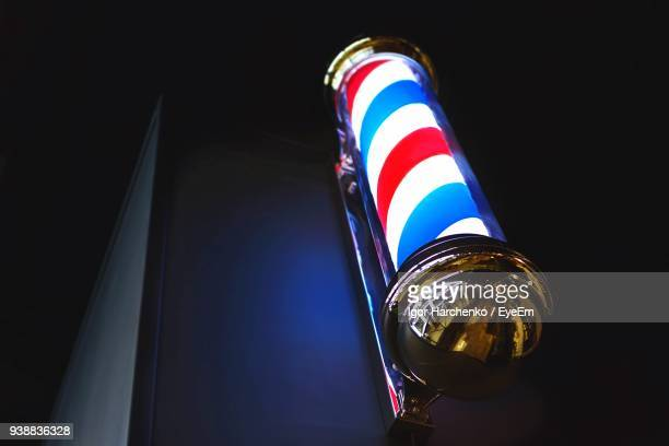 low angle view of illuminated barbers pole at night - barber pole stock photos and pictures