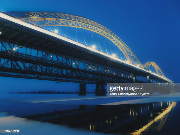 low angle view of illuminated bridge against blue sky - nizhny novgorod oblast stock photos and pictures