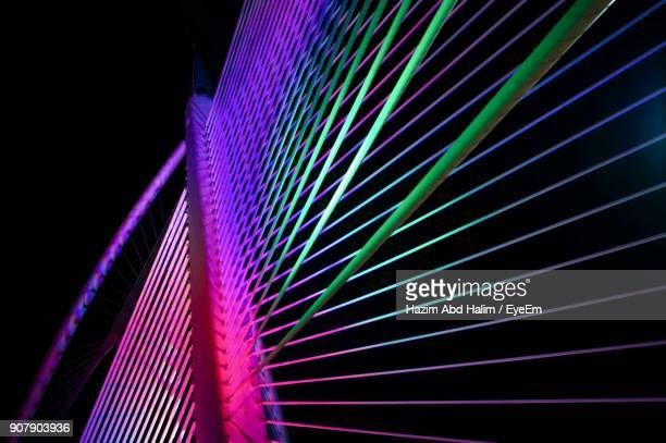 low angle view of illuminated bridge against sky at night - putrajaya stock photos and pictures