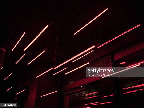 low angle view of illuminated building at night - rot stock-fotos und bilder