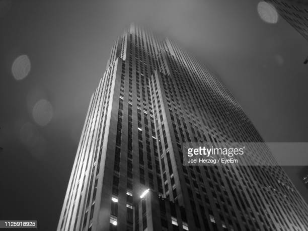 low angle view of illuminated buildings against sky at night - rockefeller center stock pictures, royalty-free photos & images