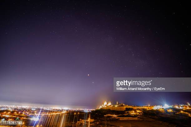 low angle view of illuminated buildings against sky at night - william moon stock pictures, royalty-free photos & images