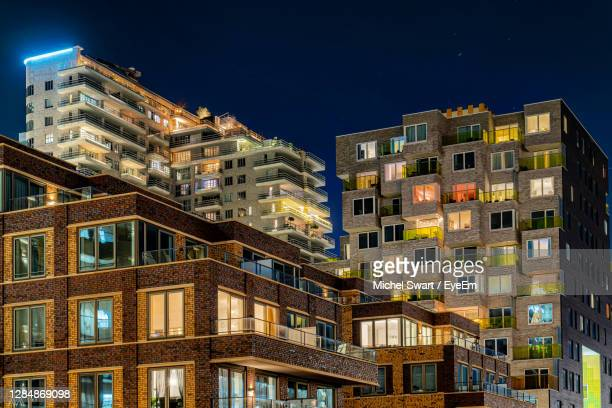 low angle view of illuminated buildings against sky at night - amsterdam stock pictures, royalty-free photos & images