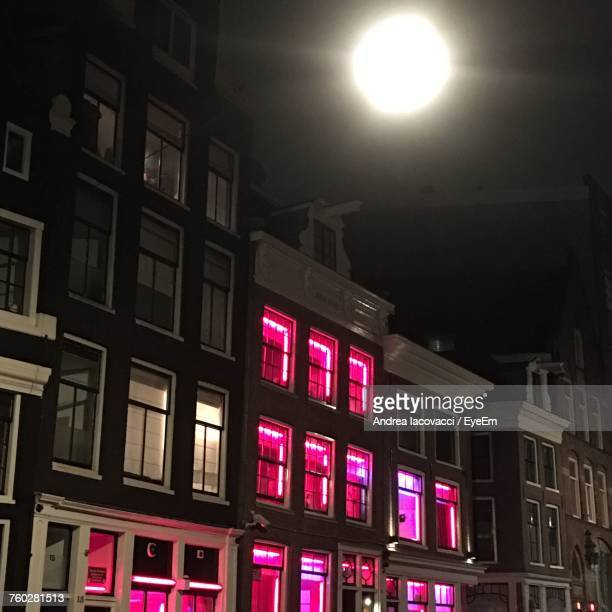 low angle view of illuminated buildings at night - red light district stock photos and pictures