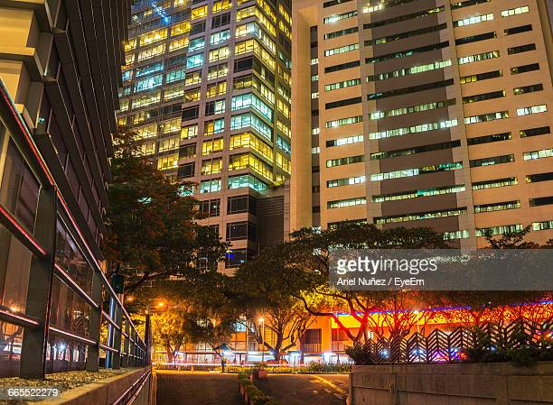 low angle view of illuminated buildings in city - makati stock photos and pictures